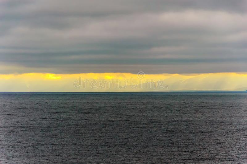 A bright band of light from under the clouds over lake Baikal. Autumn nature of Eastern Siberia. Day in November. stock photos