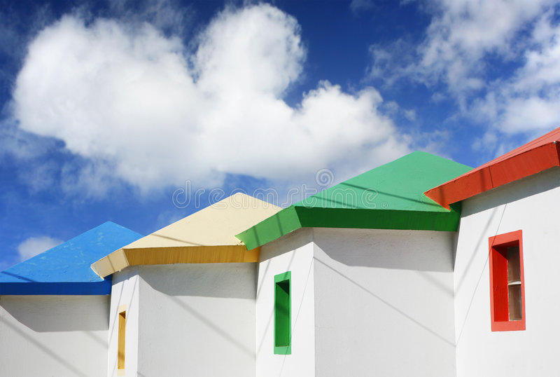 Bright Beach Huts. With dramatic blue sky royalty free stock images