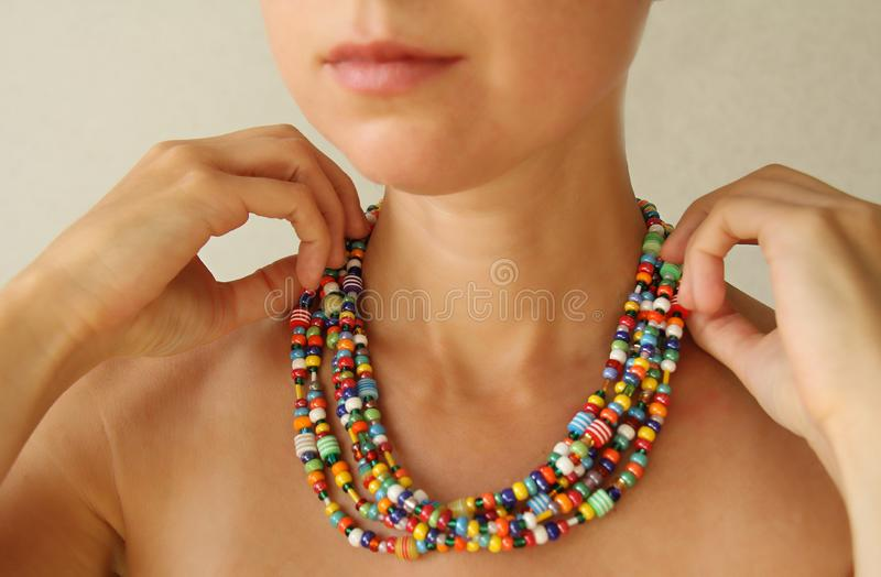 Bright beads of Murano glass on a young girl. A girl dresses and button beads, jewelry.  stock photo