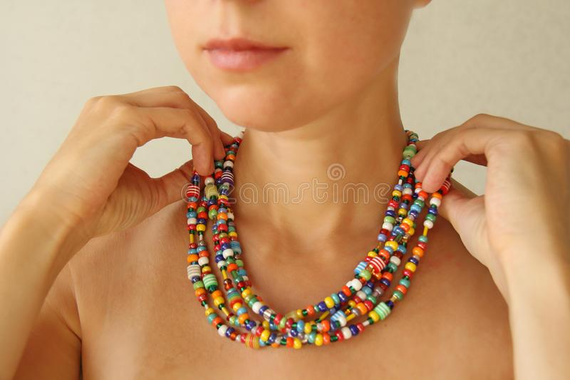 Bright beads of Murano glass on a young girl. A girl dresses and button beads, jewelry.  royalty free stock photo