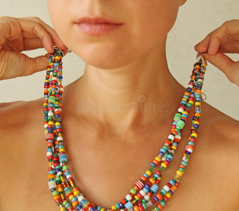 Bright beads of Murano glass on a young girl. A girl dresses and button beads, jewelry.  royalty free stock image