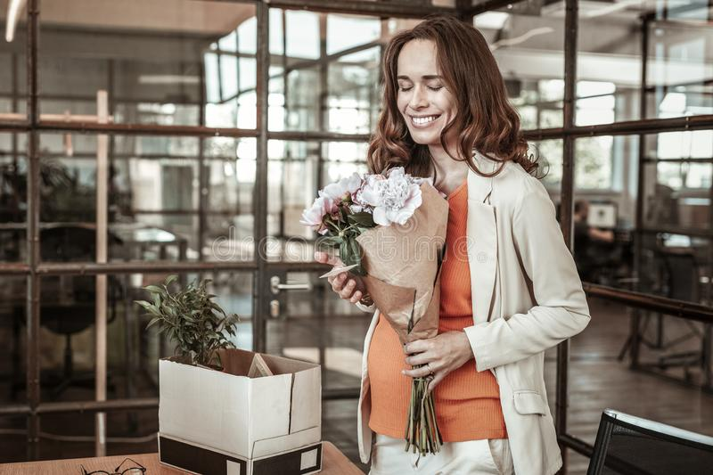Bright beaming lady being extremely happy while carrying bouquet of flowers royalty free stock photos