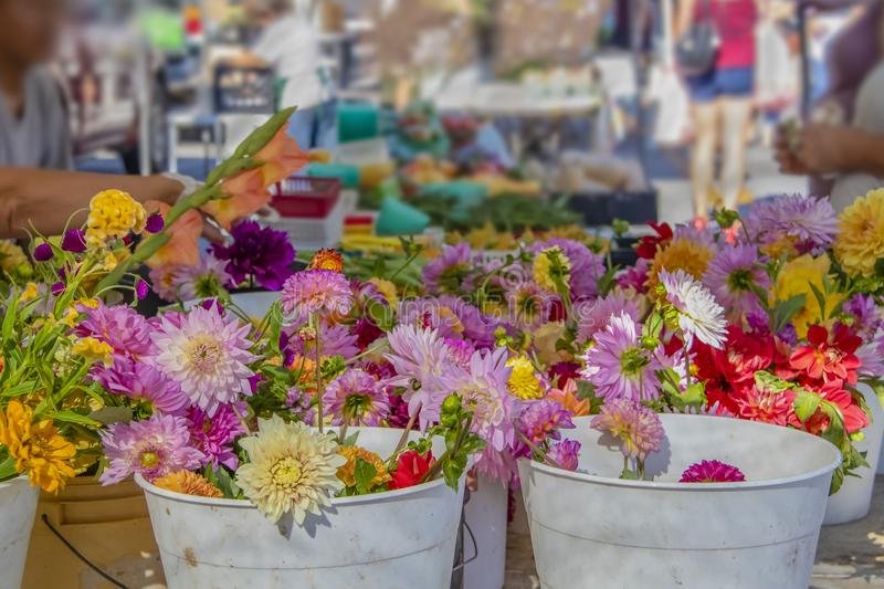 Bright beautiful flowers in buckets of water in focus in foreground with blurred - bokeh busy outdoor market stretching out behind stock photo
