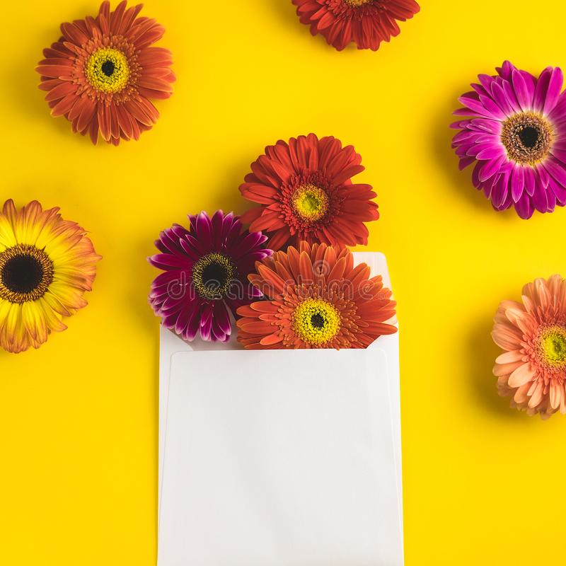 Bright beautiful gerbera flowers and paper card on a sunny yellow background. Mother`s Day, Valentine holiday. Place for stock photo