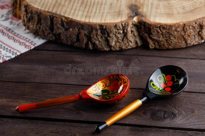 Bright and beautiful Khokhloma painted wooden utensils. Two wooden spoons with a traditional Russian pattern on a wooden royalty free stock images