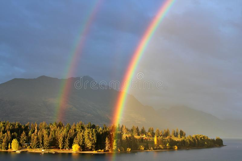Real double rainbow in cloudy sky, Queenstown, New Zealand royalty free stock photography