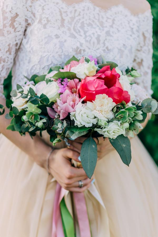 Bright beautiful wedding bouquet. Bride holds a wedding bouquet in her hands.  royalty free stock image