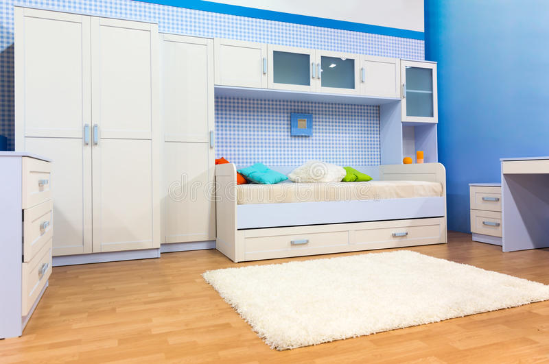 Bright bedroom with a bed and cupboard stock images