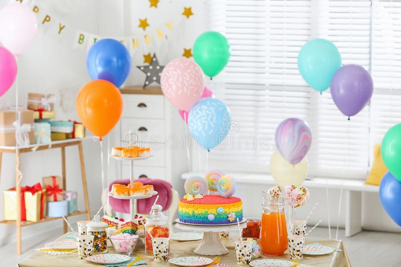 Bright birthday cake and other treats on table in room royalty free stock image