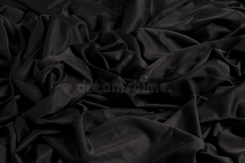 Bright black fabric with ripples and texture with hard light and dark light royalty free stock photos