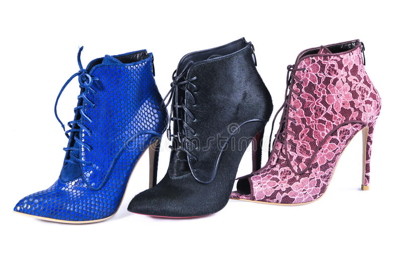 Bright blue, burgundy lace and black fur ankle boots. Footwear of three different colors and materials royalty free stock photo