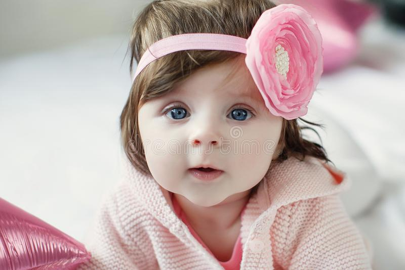 Bright blue eyed beauity 6 month old baby girl looks closely at the camera royalty free stock images