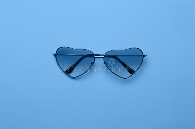 Bright blue heart-shaped glasses on a paper background stock photos