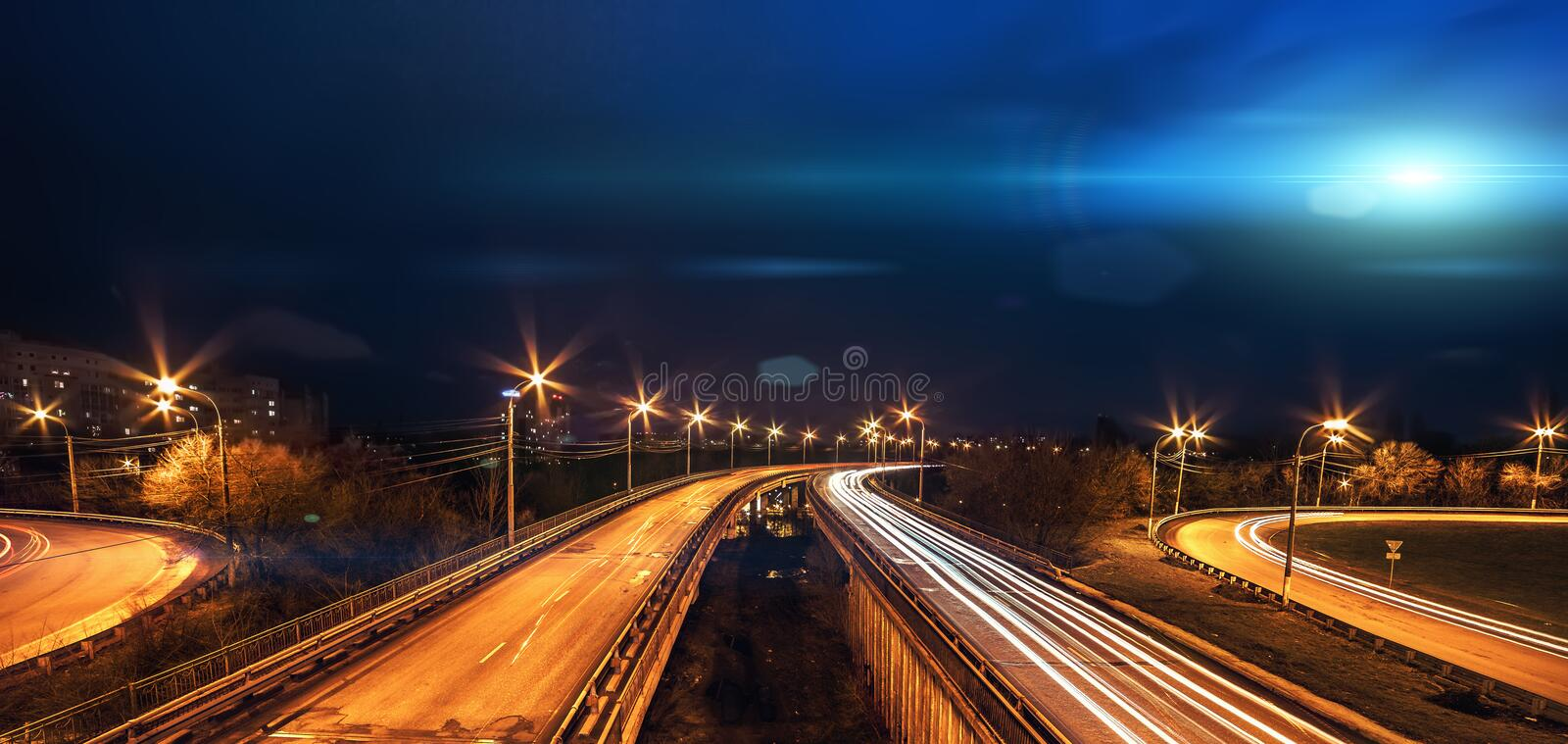 Bright blue light UFO ship fly above city and blurred road traffic at night. Panoramic photo royalty free stock photography
