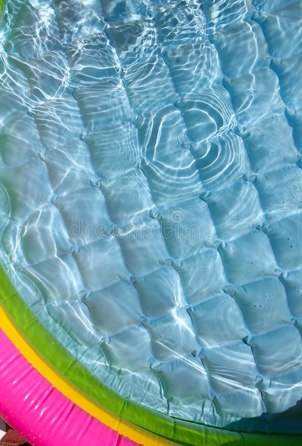 Bright blue paddling pool surface with water ripples royalty free stock image