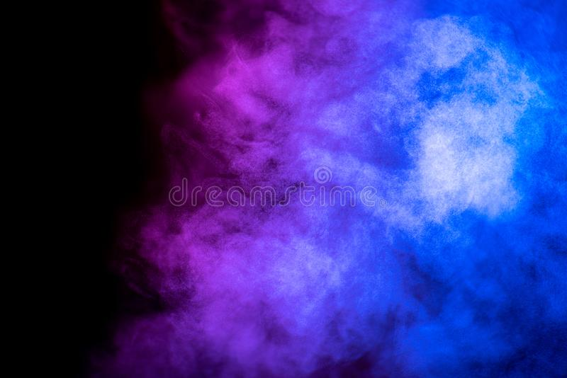 Bright blue and purple smoke isolated on black background. Is macro, steam, mist, effect, design, fog, light, cloud, white, shape, magic, swirl, air, texture royalty free stock photos