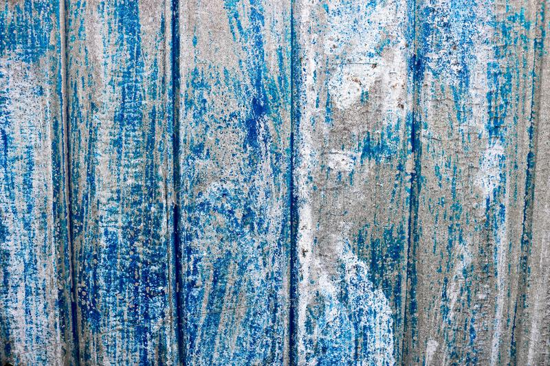 Bright blue saturated relief texture of a beautifully painted metal surface with vertical stripes and shabby erased paint. Background stock photo