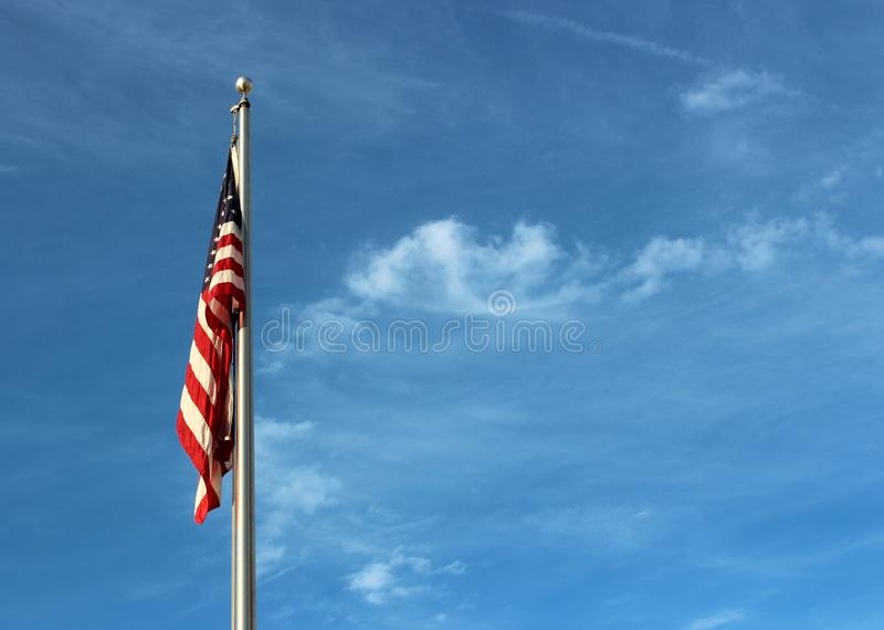 Bright blue skies with wispy cloud serve as background to the American flag stock photo