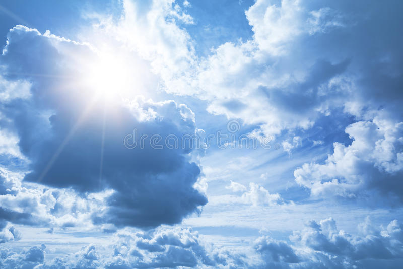 Bright blue sky background with white clouds and sun stock photo