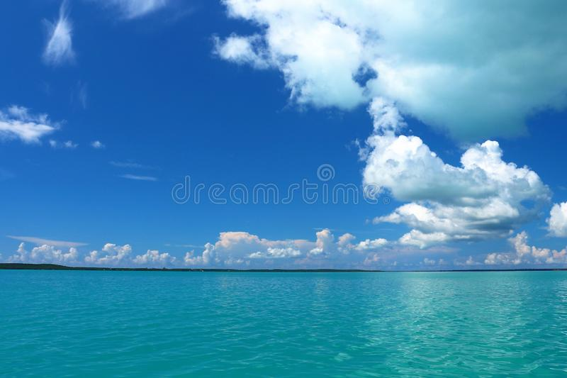 Bright blue sky with broken clouds over crystal clear blue water in Rock Sound Eleuthera stock photo
