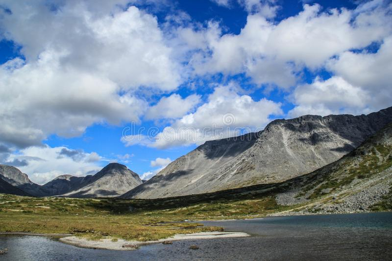 Bright blue sky with clouds over the mountain and lake royalty free stock photos