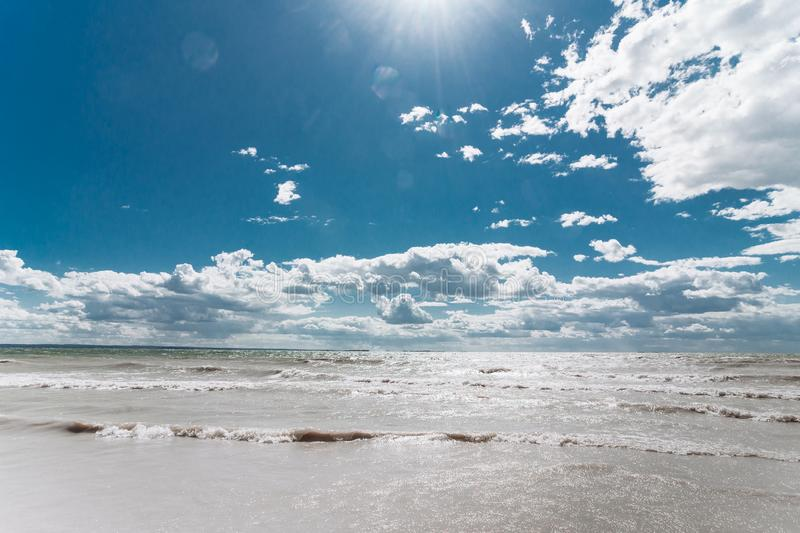 Bright blue sky with clouds over the sea with waves royalty free stock images