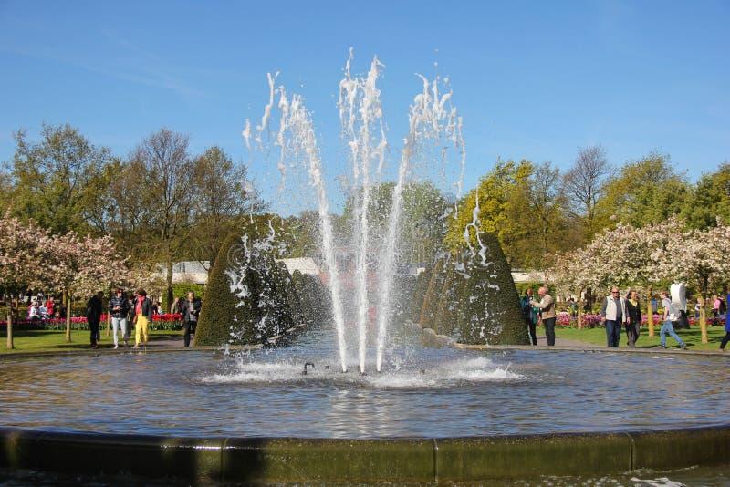 Bright blue sky over water pool fontain in spring time in Keukenhof flower garden. Happy people walking in park stock image