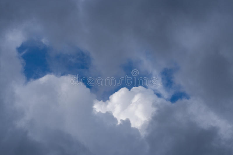 Bright blue sky and white cloud peek out from clearance in dark. Bright blue sky and white cloud peek out from clearance in grey dark clouds stock photography