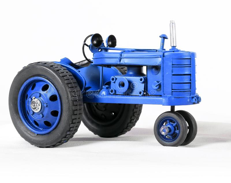 Blue Toy Tractor on White. Bright Blue Toy Miniature Tractor with Shadows on White royalty free stock image