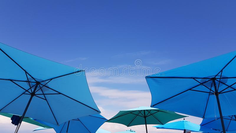 Bright blue and turquoise color parasols on blue sky backgrounds stock photos