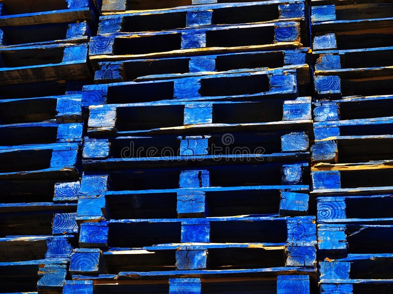 Bright blue wooden shipping palettes stock photography