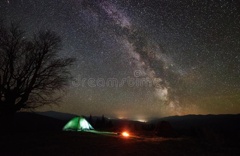 Night camping in the mountains. Hikers having a rest in tourist tent under starry sky near campfire stock photos
