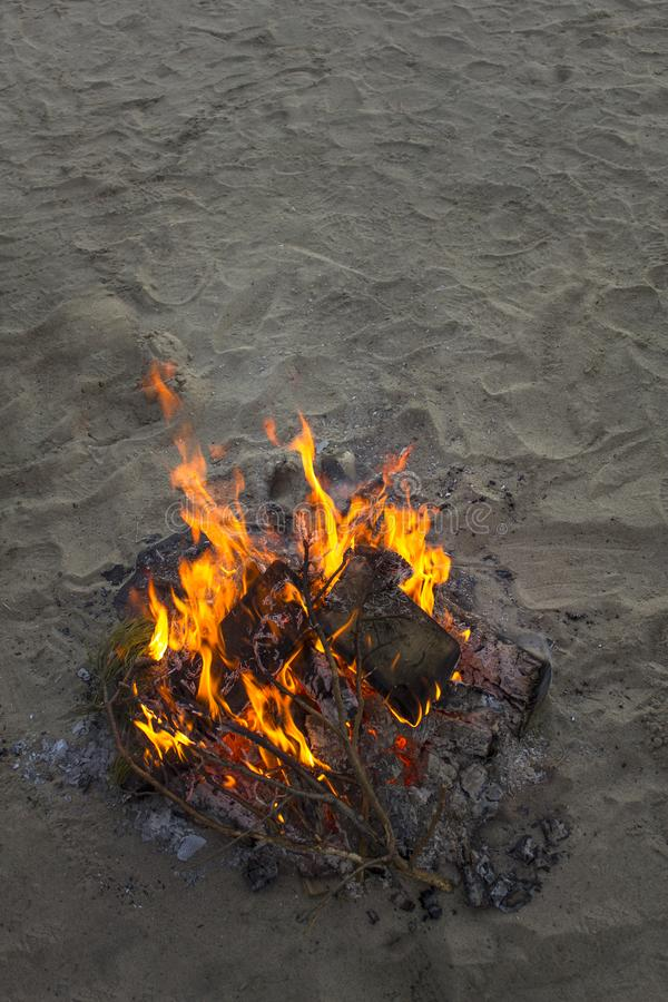 Bright bonfire on gray sand close up in the evening stock photography