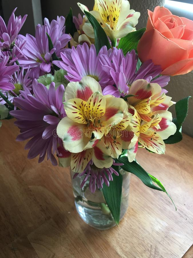 Bright bouquet of spring flowers in glass vase stock photography