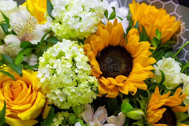Bright bouquet with yellow sunflowers and rose, pink eustoma and green viburnum floral background. Bright bouquet with yellow sunflowers and rose, pink eustoma stock photo