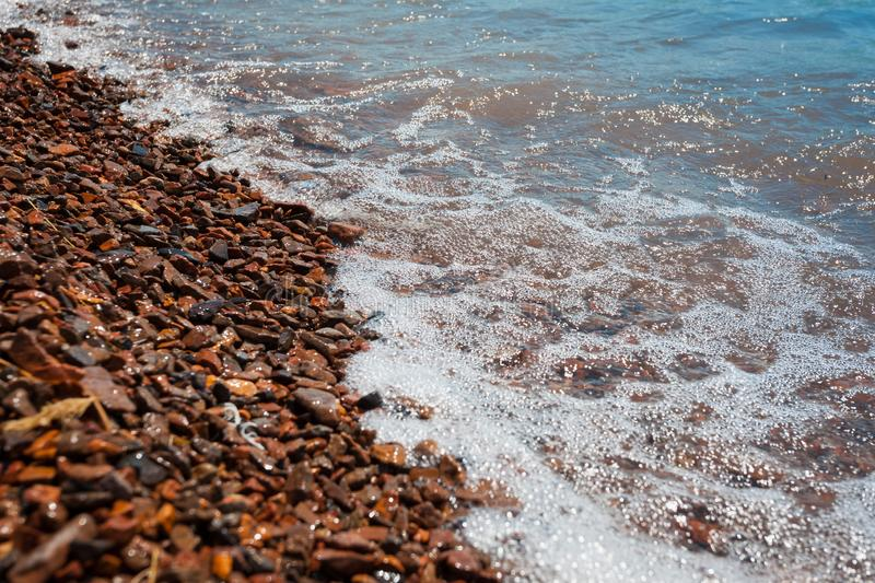 Bright brown sea pebbles covered with soothing waves royalty free stock image