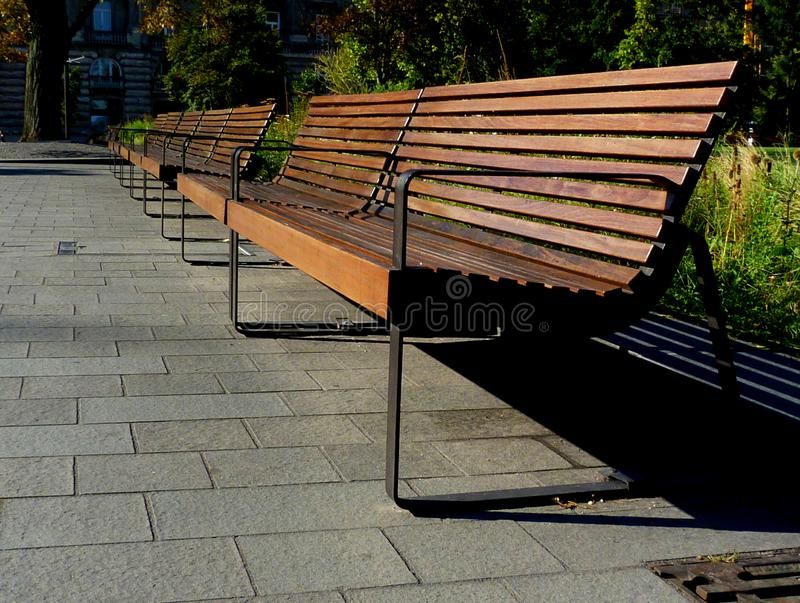 Bright brown wooden park benches in diminishing perspective with green landscape. Bright brown wooden park benches in diminishing perspective. green landscaped stock photo