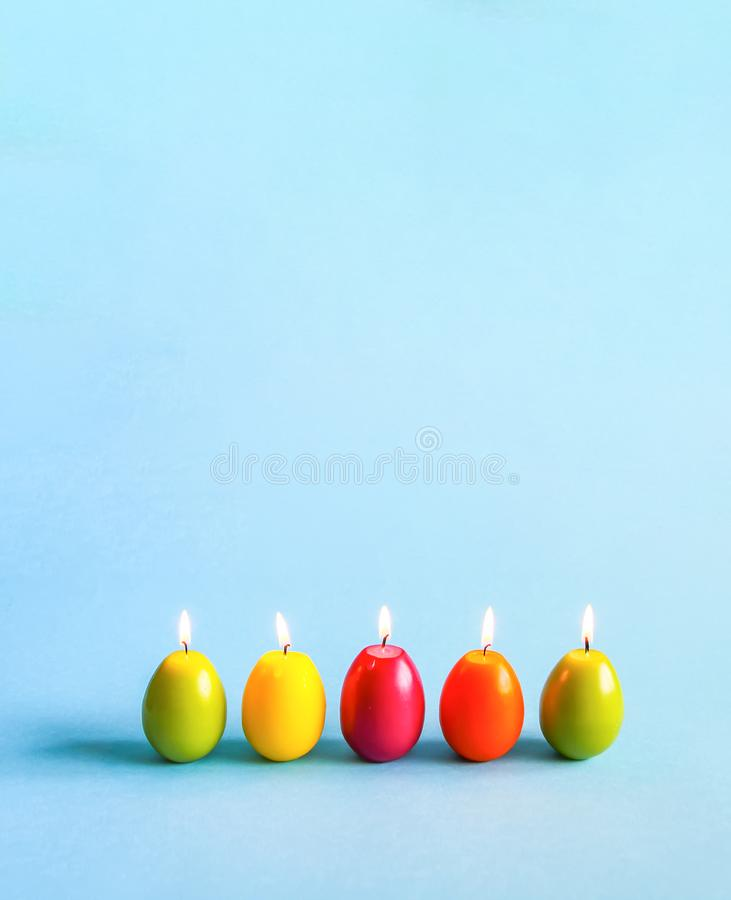 Bright burning paraffin candles in the shape of colorful Easter eggs on blue background stock photo