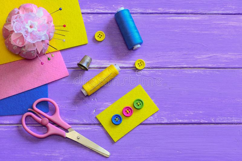 Bright buttons sewn to the yellow felt piece. Scissors, thread, thimble, needles, pins, felt pieces on a wooden background. Sewing basics. How to sew a button royalty free stock image