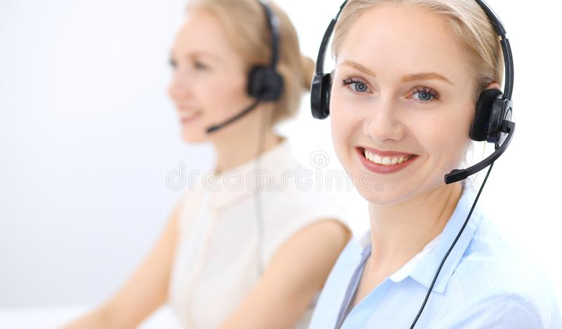 Bright call center office. Two blonde women in a headset royalty free stock image