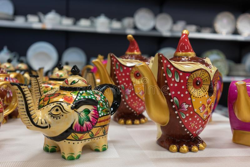 Ceramic teapots in a shop window on the background of shelves with cooking utensils. royalty free stock photos