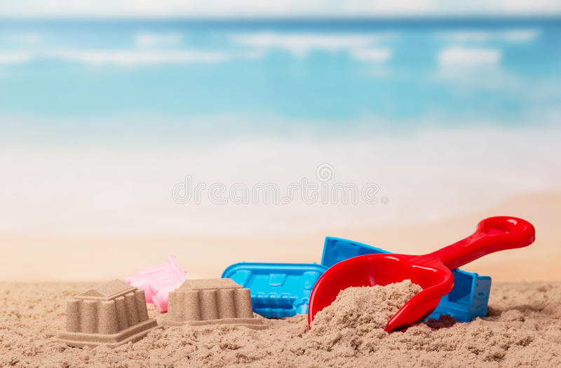 Bright children's toys in the sand against sea. royalty free stock photo