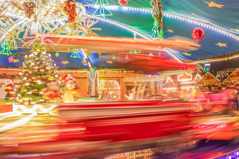 Bright christmas carrousel at the Christmas fair. Defocused xmas abstract. Blurred background. Bright christmas carrousel at the Christmas fair. Defocused xmas stock photo