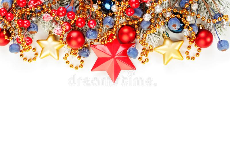 Bright Christmas composition border isolated. Colorful banner background with green Xmas tree twig, holly berries, red and blue stock photos