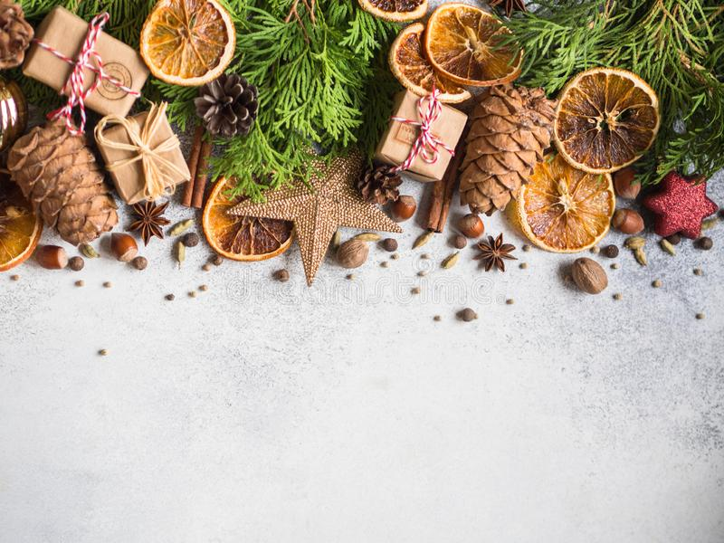 Bright Christmas or New Year background with thuja branches, Christmas decorations, spices, nuts, dried orange slices, pine cones. royalty free stock photography
