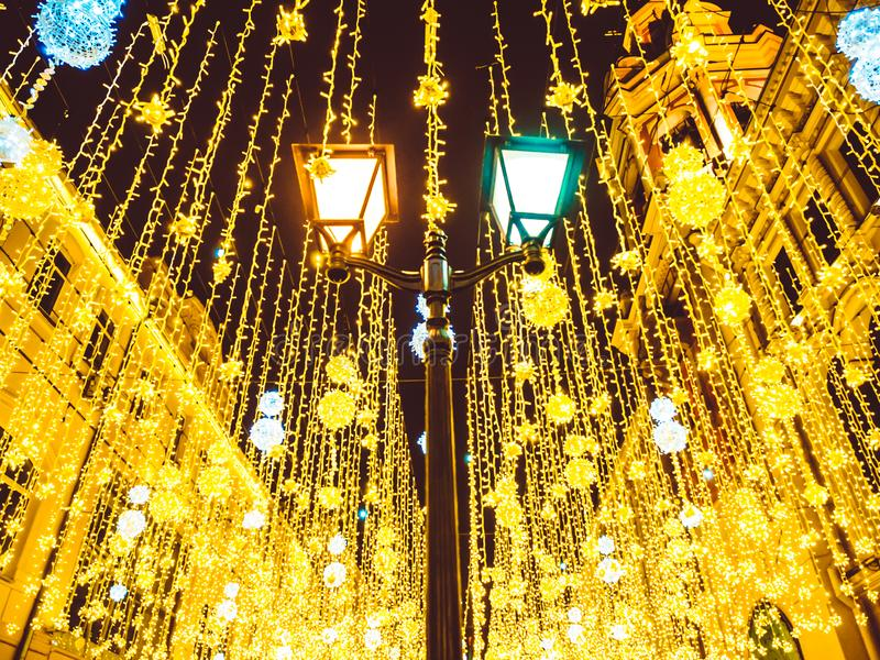 Bright Christmas Street Illumination on the facade of the buildings. Burning lanterns on Nikolskaya street in Moscow. The City is Decorated for the royalty free stock image