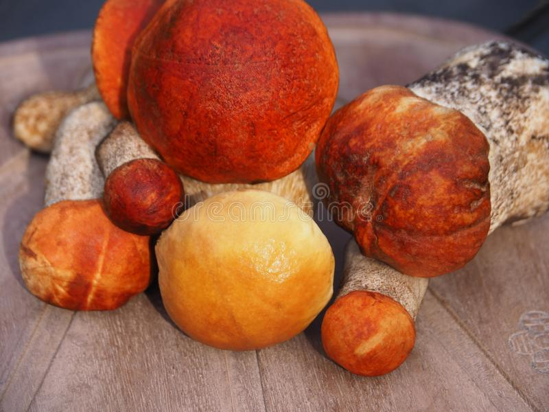 A bunch of mushrooms. Bright, clean, beautiful edible mushrooms lie on a wooden background. Forest white mushroom and red boletus close-up royalty free stock photos