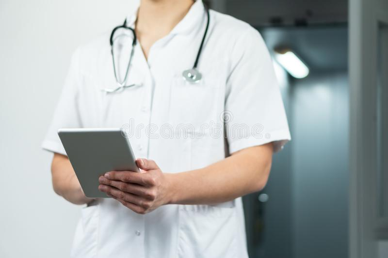 Bright close up of male doctor in uniform with stethoscope and using computer tablet in hospital. Modern medical concept stock photography