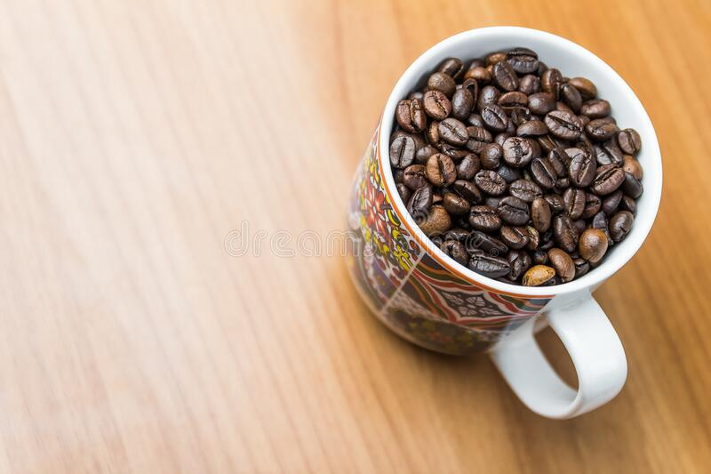 Bright close up shot of vintage coffee mug with coffee beans wooden background. Top down vied bright close up shot of coffee mug with coffee beans against wooden royalty free stock image