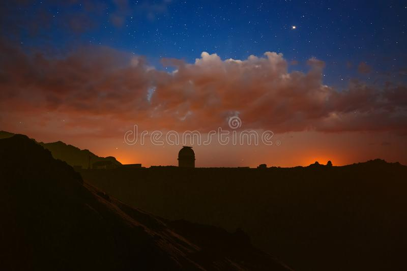 Bright clouds at night and stars in the sky. Observatory in the mountains to explore space on a bright background of the Milky Way.  stock images